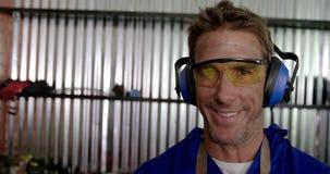 Männlicher Mechaniker, der Kamera in der Reparaturgarage 4k betrachtet stock video footage