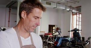 Männlicher Mechaniker, der Laptop in der Motorradreparaturgarage 4k verwendet stock video