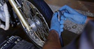 Männlicher Mechaniker, der Motorrad in der Reparaturgarage 4k repariert stock video