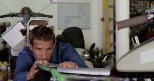 Männlicher Mechaniker, der Motorrad in der Reparaturgarage 4k repariert stock video footage
