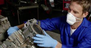 Männlicher Mechaniker, der Motorradmaschine in der Reparaturgarage 4k repariert stock video