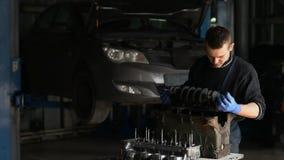 Männlicher Mechaniker sammelt einen umgebauten Motor für das Auto stock video