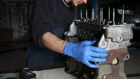 Männlicher Mechaniker sammelt einen umgebauten Motor für das Auto stock footage