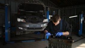 Männlicher Mechaniker sammelt einen umgebauten Motor für das Auto stock video footage