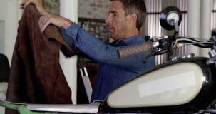 Männlicher Mechanikerfestlegungs-Motorradsitz in der Reparaturgarage 4k stock video