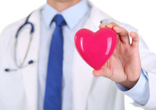 Männlicher Medizindoktor übergibt das Halten des roten Spielzeugherzens lizenzfreie stockfotos