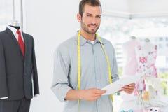 Männlicher Modedesigner, der Skizze im Studio hält Stockbilder
