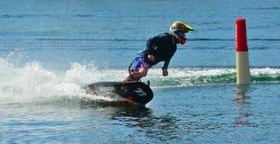 Männlicher Motosurf-Konkurrent, der Ecke mit der Geschwindigkeit herstellt viel Spray nimmt lizenzfreie stockfotografie