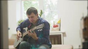 Männlicher Musiker, der akustische Lebensstilgitarre spielt Mann, der Akustikgitarrezeitlupevideo spielt im Raum sitzt auf stock footage