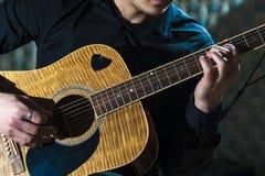 Männlicher Musiker, der auf Akustikgitarre spielt Stockfotos