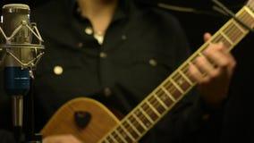 Männlicher Musiker, der auf Gitarre hinter Mikrofon spielt stock footage