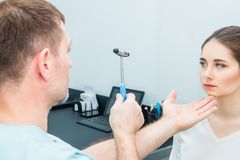 Männlicher Neurologedoktor, der junges weibliches geduldiges ` s Nervensystem unter Verwendung eines Hammers kontrolliert Neurolo Lizenzfreies Stockfoto