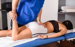 Männlicher Osteopath, der das Knie eines Patienten behandelt stockbilder