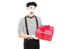 Männlicher Pantomimekünstler, der eine Geschenkbox hält und Kamera betrachtet Lizenzfreies Stockfoto