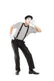 Männlicher Pantomimekünstler, der versucht, etwas zu hören Lizenzfreies Stockfoto