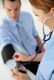 Männlicher Patient, der seinen Blutdruck genommen erhält Stockfotografie