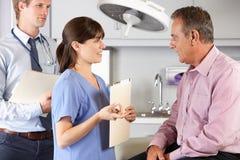 Männlicher Patient, der von Doktor und vom Internierten überprüft wird Lizenzfreie Stockfotografie