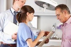 Männlicher Patient, der von Doktor und vom Internierten überprüft wird Lizenzfreies Stockfoto