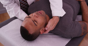 Männlicher Patient des Afroamerikaners, der Nackenschmerzen durch chiro überprüfen lässt Stockfotografie