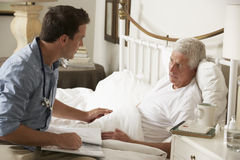Männlicher Patient Doktor-Talking With Senior im Bett zu Hause Stockfoto