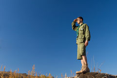 Männlicher Pfadfinder Standing auf Felsen, das Feld beobachtend Lizenzfreies Stockfoto