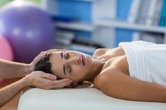 Männlicher Physiotherapeut, der dem weiblichen Patienten Kopfmassage gibt Lizenzfreies Stockbild