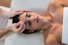 Männlicher Physiotherapeut, der dem weiblichen Patienten Kopfmassage gibt Stockbild