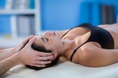 Männlicher Physiotherapeut, der dem weiblichen Patienten Kopfmassage gibt Lizenzfreie Stockfotos