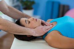 Männlicher Physiotherapeut, der dem weiblichen Patienten Kopfmassage gibt Lizenzfreie Stockfotografie