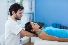 Männlicher Physiotherapeut, der dem weiblichen Patienten Kopfmassage gibt Lizenzfreies Stockfoto