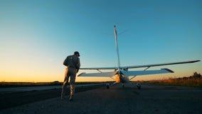 Männlicher Pilot geht einen Doppeldecker umher und überprüft seine Zustand auf einer Rollbahn 4K stock video footage