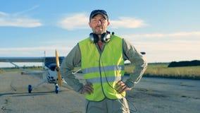 Männlicher Pilot trägt die Kopfhörer, die oben auf einem Flugplatz, Abschluss stehen stock footage