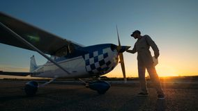 Männlicher Pilot wischt den Propeller eines Flugzeugs, Seitenansicht ab stock video footage