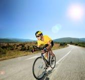 Männlicher Radfahrer, der ein Fahrrad auf eine offene Straße an einem sonnigen Tag reitet Stockfotos
