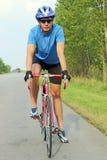 Männlicher Radfahrer, der ein Fahrrad auf eine Straße reitet Stockfotografie
