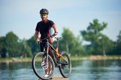 Männlicher Radfahrer, der Pause nahe bei Fahrrad nahe Stadtsee macht Lizenzfreies Stockfoto