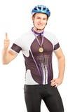 Männlicher Radfahrer des Siegers mit einer goldenen Medaille, die einen Daumen aufgibt Lizenzfreie Stockfotos