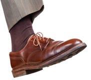Männlicher rechter Fuß im braunen Schuh unternimmt einen Schritt Stockfotos