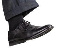 Männlicher rechter Fuß im schwarzen Schuh unternimmt Schritt Lizenzfreie Stockfotos