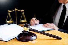 Männlicher Rechtsanwalt, der mit Vertragspapieren arbeiten und Gesetzbuch in einem Gerichtssaal lesen, Gerechtigkeit und Gesetzes lizenzfreie stockfotografie