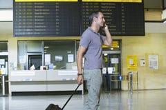 Männlicher Reisender, der Mobiltelefon durch Flug-Status-Brett verwendet Stockbild
