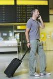 Männlicher Reisender, der Mobiltelefon durch Flug-Status-Brett verwendet Stockfotografie