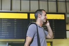 Männlicher Reisender, der Mobiltelefon durch Flug-Status-Brett verwendet Stockfoto