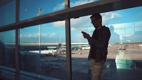 Männlicher Reisender liest Nachrichtenband in den sozialen Netzwerken durch Smartphone im Flughafen