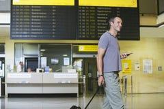 Männlicher Reisender mit Mobiltelefon durch Flug-Status-Brett Stockbild