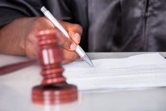 Männlicher Richter Writing On Paper im Gerichtssaal Lizenzfreies Stockfoto