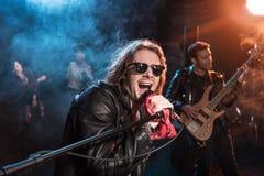 Männlicher Sänger mit dem Mikrofon und Rock-and-Roll-Band, die Hardrockmusik durchführen lizenzfreie stockfotografie