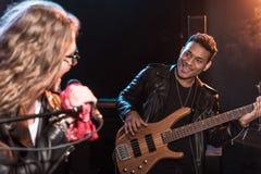 Männlicher Sänger mit dem Mikrofon und Rock-and-Roll-Band, die Hardrockmusik durchführen stockfotos