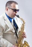 Männlicher Saxo-Spieler in der Sonnenbrille, die ausdrucksvoll im Studio durchführt stockfotografie
