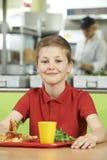 Männlicher Schüler, der bei Tisch beim Schulcafeteria-Essen gesundes L sitzt Stockbilder